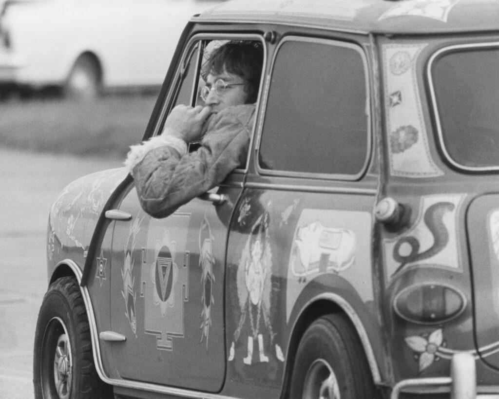 John Lennon met de Mini van George Harrison.